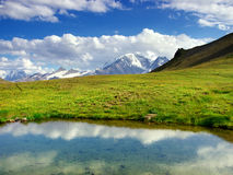 Big lake. On green meadow amongst mountains Royalty Free Stock Photo