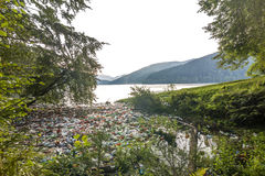 Big lake in mountains with lot of garbage trash cans and bottles Stock Images