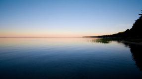 Big lake at sunset. A large lake at sunset. Reflection of the forest in still water. Peace and quiet Stock Photography