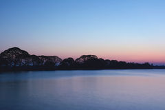 Big lake at sunset near ancient city Anuradhapura, Sri Lanka. Tr. Opical trees in dusk Stock Photo