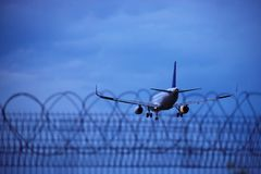 Landing airplane behind the security fence royalty free stock photography