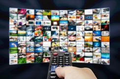 Big LCD panel with television stream images and remote control Royalty Free Stock Photography