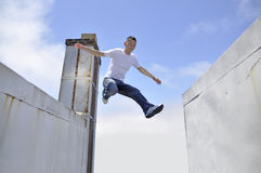 Big leap. Asian young man making a giant leap in between buildings Stock Images