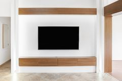 Big led TV on white wall. With wooden shelf royalty free stock photography