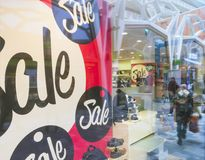 Signs of sale in shop windows of shoe store. Big letters indicate sale in shop windows of shoe store Royalty Free Stock Photo