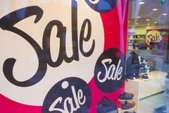 Signs of sale in shop windows of shoe store. Big letters indicate sale in shop windows of shoe store Stock Photos