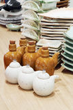 Big and little clay pots and square plates at table Stock Photo