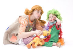 Big and little clown are playing. Colorful dressed Mother and daughter playing. Isolated over white Stock Image