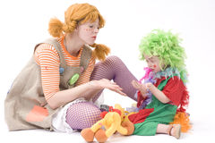 Big and little clown are playing II. Colorful dressed Mother and daughter playing. Isolated over white Stock Photo