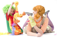 Big and little clown are playing V. Colorful dressed Mother and daughter playing. Isolated over white Stock Image