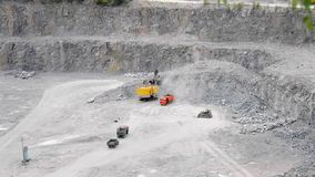Big loader pours in your bucket rubble. In a granite quarry stock video