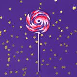 Big lollipop on solid ultra violet background with golden sprinkles. Square royalty free stock photo
