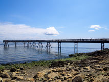 Big Long Pier reaching out into the ocean on a sunny day with blue skies background. Pier extending into the ocean with people on it on a beautiful summer day Royalty Free Stock Photography