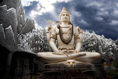 Big Lord Shiva statue in Bangalore. Big Lord Shiva statue sitting in lotus with trident in his hand and cobra near by. Dramatic sky at background with ray on Royalty Free Stock Photos
