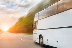 Big luxury comfortable tourist bus driving through highway on bright sunny day. Blurred motion road. Travel and coach