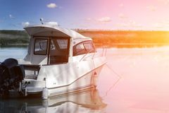 Big luxury fishing boat with cabin moored near river or lake shore in still water. Blue sky on the background. Summer stock photography