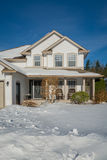 Big luxury house with front yard in snow. Residential house on winter sunny day Royalty Free Stock Images