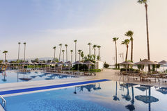 Big  luxury  pool with  palms with sunset sky Royalty Free Stock Photos