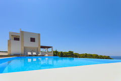 Big luxury pool with villa. Big pool and modern luxury villa with blue sky and trees stock photo