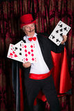 Big magic trick. Mature magician on stage performing a magic trick with cards royalty free stock images