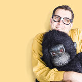 Big male goof cuddling toy gorilla. Comfort zone. Big goofy man cuddling soft toy gorilla on yellow background. Comfort zone concept Stock Image