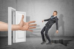 Big male open hand reaching through white doorway to catch young businessman who is falling into earth crack on grey. Wall background. Digital art. Business and royalty free stock photography