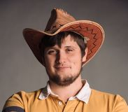 Portrait of big man in a cowboy hat and a yellow shirt. Smail Young man. The studio shot in the gray wall. A big man in a cowboy hat and a yellow shirt. Young Royalty Free Stock Photos