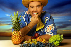 Big man eating. Fruit by the beach Stock Photo