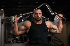 Big Man Exercise Back On Machine. Big Man In The Gym And Exercising Back On Machine - Muscular Athletic Bodybuilder Model Exercise In Fitness Center Stock Images