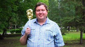 Big man holding golden balloon making the 8 number outdoor. 8th anniversary celebration party stock video