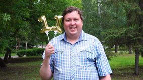 Big man holding golden balloons making the 11 number outdoor. 11th anniversary celebration party stock footage