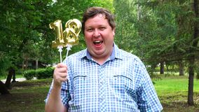 Big man holding golden balloons making the 18 number outdoor. 18th anniversary celebration party stock video