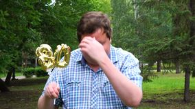 Big man holding golden balloons making the 80 number outdoor. 80th anniversary celebration party stock video