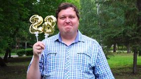 Big man holding golden balloons making the 28 number outdoor. 28th anniversary celebration party.  stock video footage