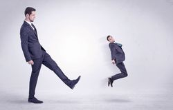 Big man kicking little himself out. Big man in suit kicking out little himself out with simple white wallpaper Royalty Free Stock Photography