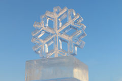 Big man-made ice snowflake and pure blue sky Royalty Free Stock Photos