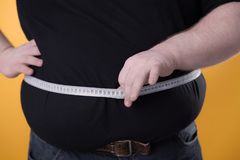 The big man makes measurements with the tape of his fat stomach. royalty free stock photography