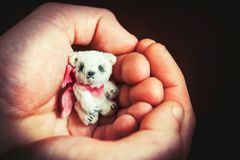 Big man palms holding small handmade teddy bear toy carefully. Indoors colored horizontal closeup image with vintage filter. Copy space Royalty Free Stock Photography