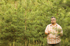 Big man walking outdoor in the forest smiling looking at camera,. Big man walking outdoor in the summer forest smiling looking at camera, toucnihg fir tree Stock Photo