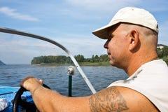 The big man at the wheel. Of the motor boat Royalty Free Stock Photos