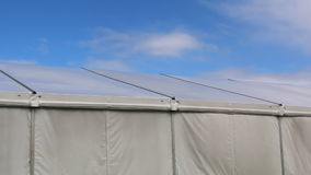 Big marquee and blue sky. Wind moving canvas of the big social or commercial event tent with blue sky and some white clouds above stock footage