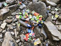 A big mass of rubbish lying all over the rocks and stones in a waterfall area. royalty free stock photos