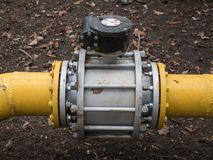 Close up shot big valve on a thick yellow gas oil water pipeline tube. Big massive valve on a thick yellow gas water oil steel metal pipelines tubes royalty free stock photo