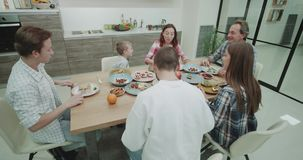Big mature family have a dinner time together they spending a good time together on the dinner table in a amazing. Kitchen design stock video footage