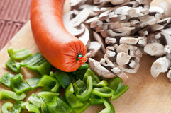 Big meat sausage and sliced vegetable Royalty Free Stock Photo