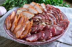 Big meat set. Homemade smoked pork-beef sausage, salted bacon, basturma chopped slices. On a wooden board with spices and herbs Royalty Free Stock Photos