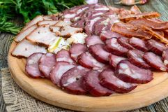 Big meat set. Homemade smoked pork-beef sausage, salted bacon, basturma chopped slices royalty free stock images