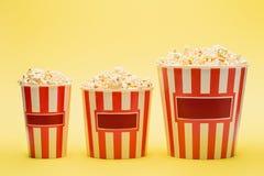 big, medium and small buckets of popcorn on yellow, cinema concept.
