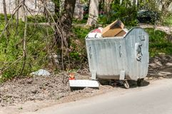 Big metal dumpster garbage can full of overflowing junk polluting the street in the city with litter.  Royalty Free Stock Photo