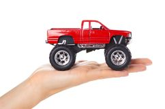 Big metal red toy car offroad with monster wheels in hand isolated on white background.  Royalty Free Stock Image
